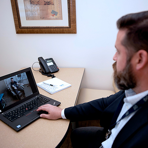 Physician consulting with patient via laptop