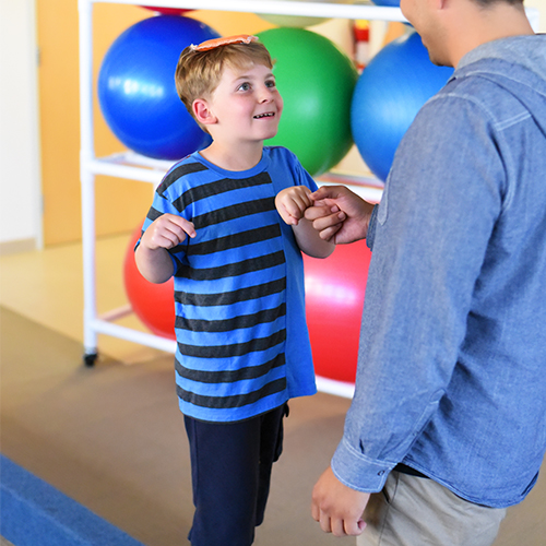 Pediatric patient working on balance with therapist